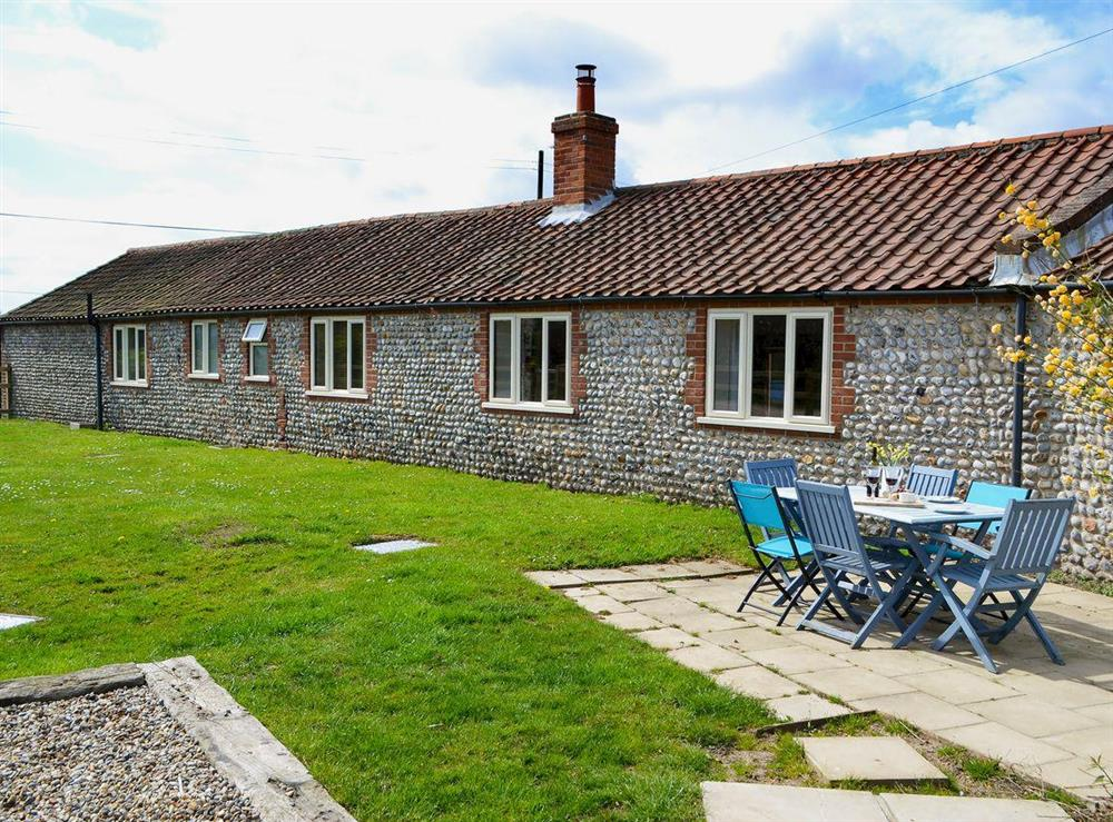 Enclosed lawned garden with sitting-out area and garden furniture at Flint Barn,