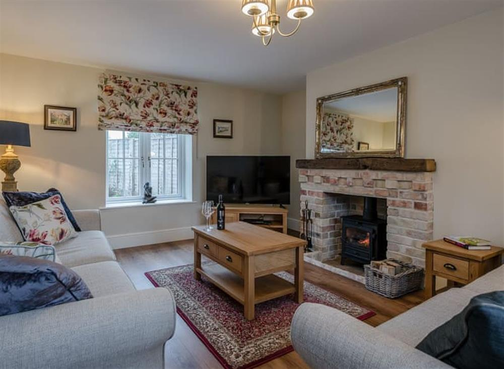 Cosy living room with wood burner at Wisteria House in Henstead, near Southwold, Suffolk